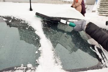 Зима. Очистка легкового автомобиля от снега после снегопада