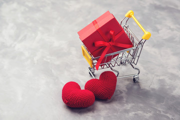 Red gift box in the shopping cart, with two knitted hearts on grey texyured background.