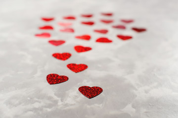 A lot of red paper hearts on grey concrete background. Valentine's Day card.