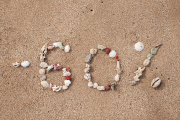Text 60 percents on sand made from shell on seashore. Concept for big sales or black friday