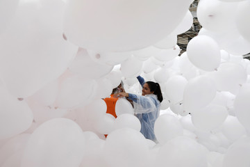 A woman prepares balloons to be released into the sky as a part of the year-end celebrations in downtown Sao Paulo