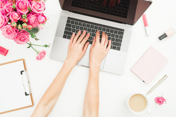 Home office desk. Woman workspace with female hands, laptop, pink roses bouquet, accessories, diary on white. Top view. Flat lay. Girl working on laptop.