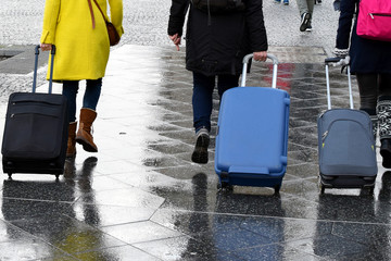 Three Women walking with suitcases outdoors on rainy day.