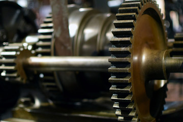 Cogwheels and axel in old mechanical system. Close up horizontal industrial image.