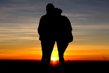 Silhouette love couple on sunset background.
