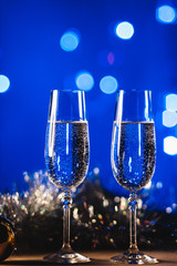 Glasses with champagne against fireworks and holiday lights - Celebrating the New Year
