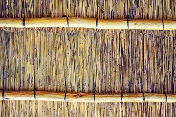 Close up shot of the inside of a thatched reet roof with cross beam enforcements. Use for backgrounds or textures with copy space.