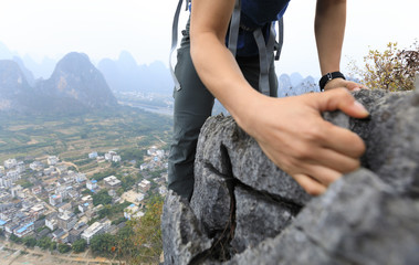 brave woman backpacker climbing rock at mountain top cliff edge