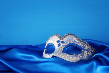 Image of elegant blue and gold venetian mask over blue silk fabric background.