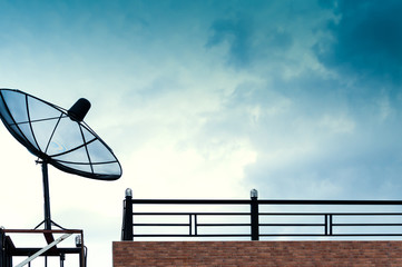 Black satellite dish or TV antennas on the building with the blue sky cloudy background.