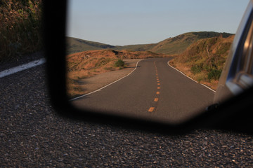 Looking into a rearview mirror at a landscape image of a deserted, divided highway heading towards the Northern California foothills near Petrolia.