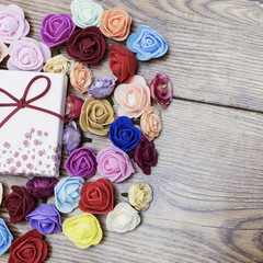 Symbol of Valentine's day. Gift box with group of roses over wooden table. Top view.