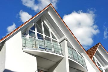 Balkon an moderner Hausfront mit Edelstahl-Glas-Geländer und Sichtschutz