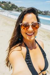 Happy woman on beach taking selfie photo