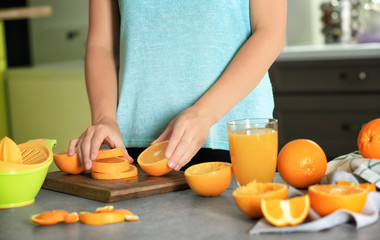 Woman with sliced orange in kitchen