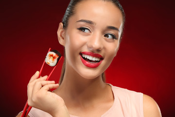 Beautiful young woman with sushi roll on color background