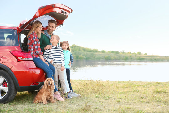 Young family with cute children and dog near car