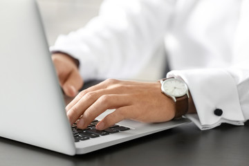 Marketing manager using laptop at table, closeup