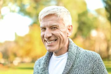 Stylish mature man in autumn park
