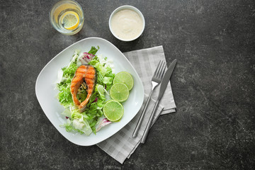 Delicious fried rainbow trout with salad and sauce on grey background, top view