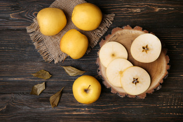Fototapete - Ripe yellow apples on wooden table, top view