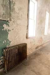 Old rust and painted heating radiator in a cement room