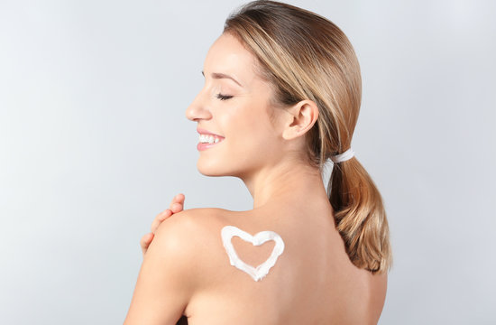 Young woman with heart made of body cream on her skin against light background