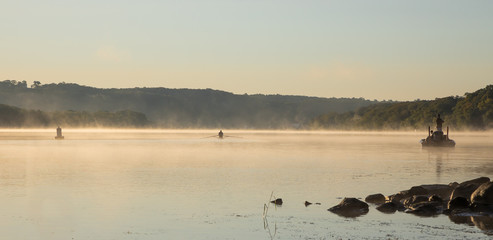 Serene Sunrise Landscape on Foggy Calm Water with Rower, Fishermen in Boat, and Buoy