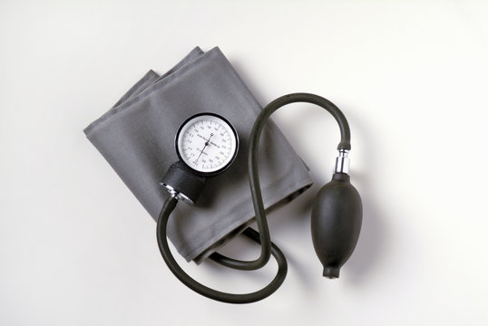 Blood Pressure Cuff on White Background.  Also known as a sphygmomanometer it is used to measure the blood pressure of patients in a medical environment.