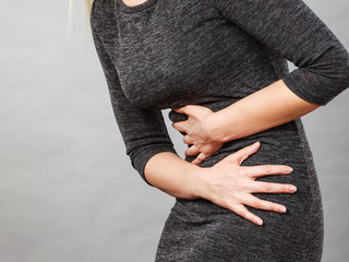 Woman having strong stomach ache. Syndroms