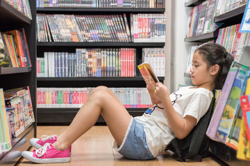 Children's education lifestyle with school girl kid reading book  sitting on the floor of bookstore...