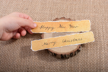 Happy new year,  Merry Christmas, written on a torn paper