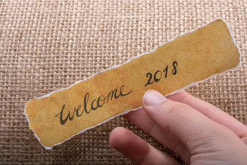 Welcome 2018 wording written on  a yellow torn paper
