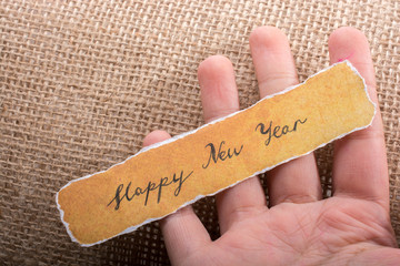 Happy new year written on a torn paper in hand