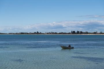 Angler fährt mit seinem Boot von rechts nach links zum nächsten Angelpunkt