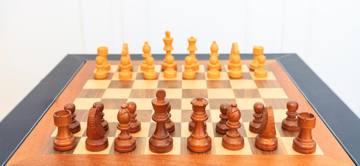 Wooden chess board with pieces on it. Leather frame, close up view, details, white background.