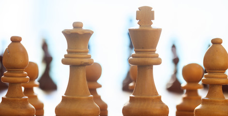 Chess pieces light brown color. Close up view with details, blurred background.