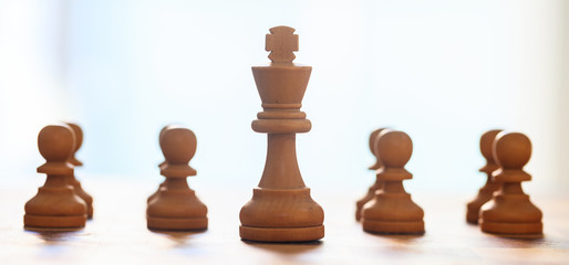 Chess pieces light brown color. Close up view of king and pawns with details. Blurred background.