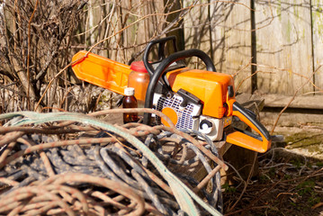 Chainsaw lies on rural bench with coils of ropes