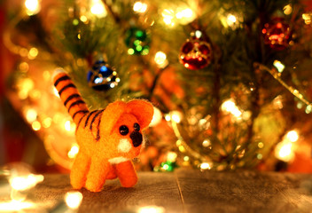 Symbol of new years 2022  Striped Tiger. New years greetings background. Fancy handmade toy from wool on bokeh Christmas background. Copyspace for congratulations.