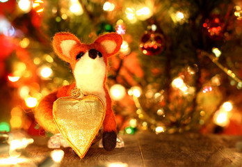 Fox toy. Love heart. New years greetings background. Fancy handmade toy from wool on bokeh Christmas background. Copyspace for congratulations.