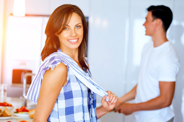 Young woman smiling standing with kitchen towel