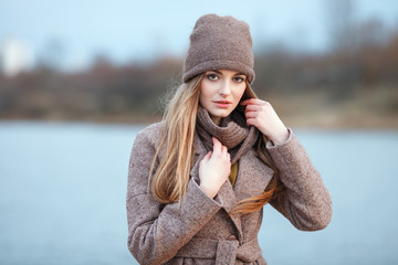 Stylish blonde woman in trendy urban outwear posing cold weather on the river bank. Vintage filter film saturated color. Fall mood concept.