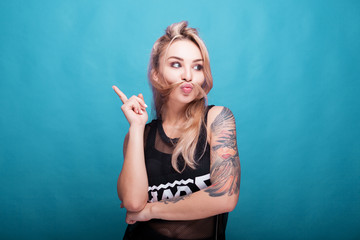 Young blonde woman with hair mustache making silly face and pointing up on blue cyan background in studio photo