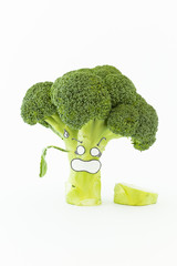 Closeup of fresh green broccoli with scared cartoon style face on white background