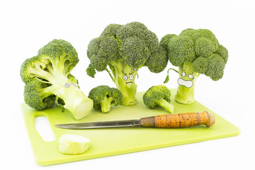 Closeup of fresh green broccoli with scared cartoon style faces on a green plastic cutting board and a vintage kitchen knife with rusty blade on white background
