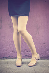 Woman legs with pastel yellow panties and mary jane shoes over a violet wall background - Funny tights and flat shoes - Female legs in a fashion, cute, retro stylish look