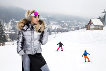 Beautiful young woman in winter, ski clothing on a background of mountains. The woman is skiing.