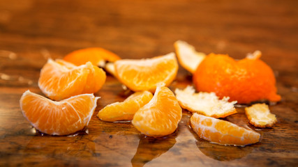 peeled tangerine on a wet wooden table