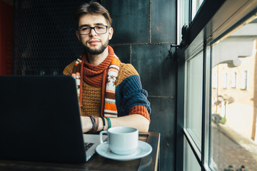 Handsome bearded male freelancer in glasses dressed in the warm sweater relaxing, drinking coffee and trying to get working with laptop near the big window in loft interior studio.